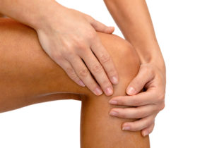close up of female hands holding knee with knee pain
